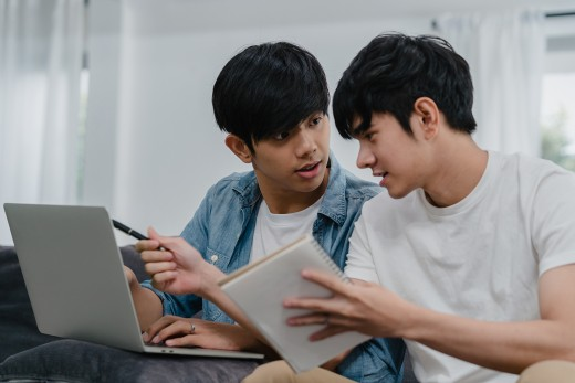 Young Asian Gay couple working laptop at modern home. Asia LGBTQ+ men happy relax fun using computer and analyzing their finances in internet together while lying sofa in living room at house concept.